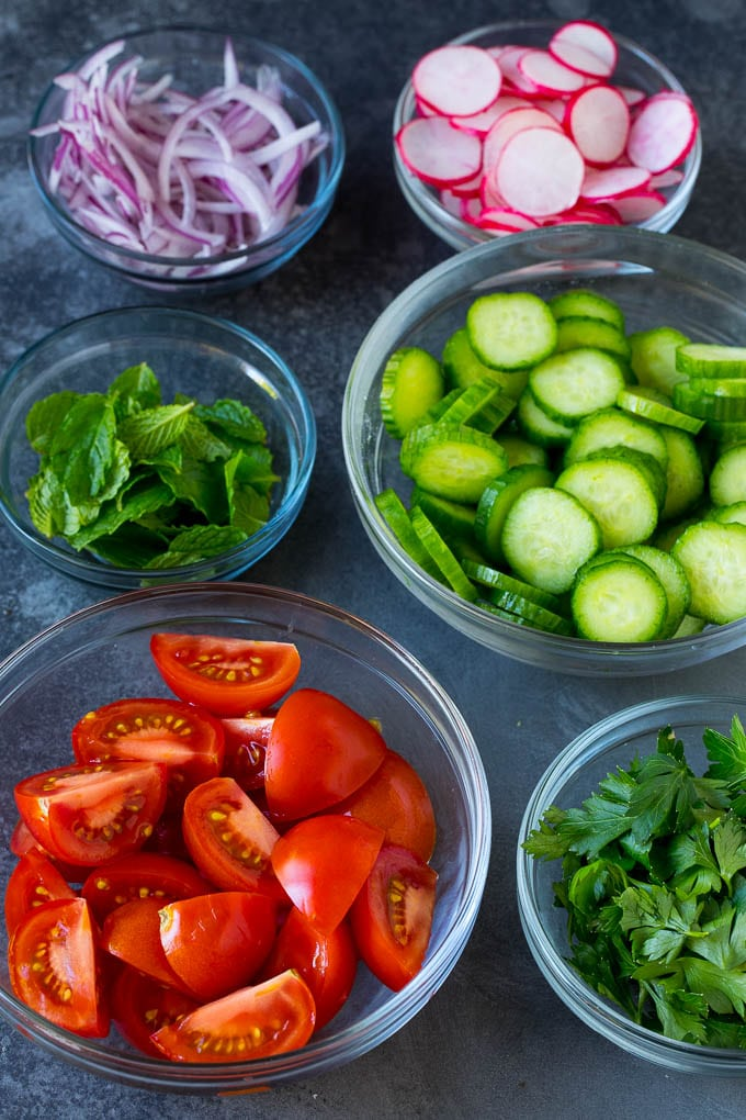 Bowls of cucumber, tomato, onion, radish and herbs.