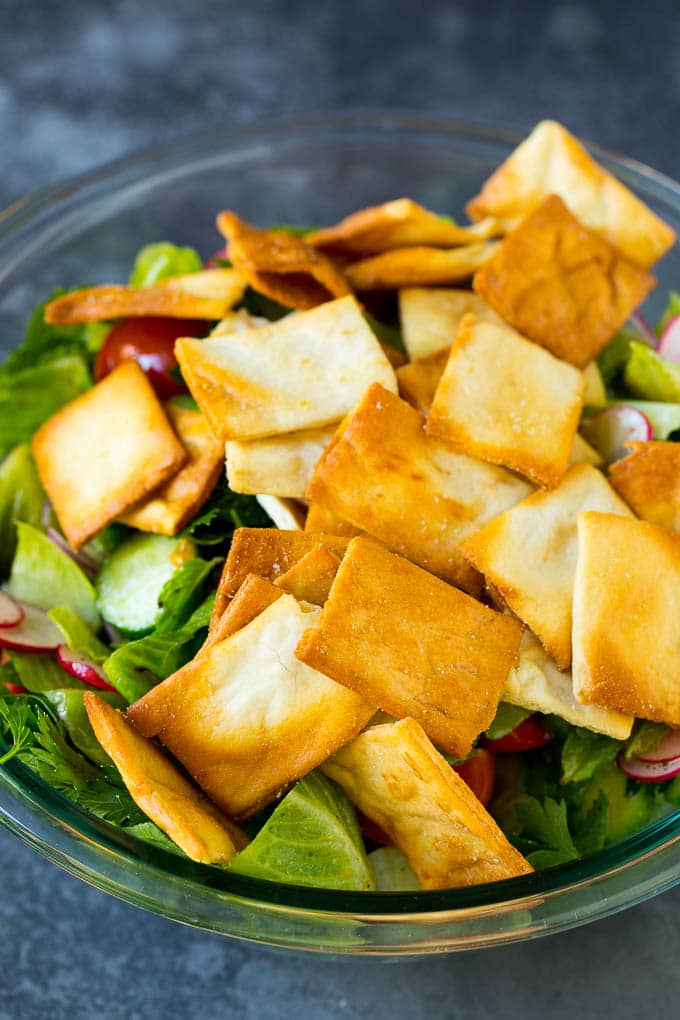 Pita chips on top of a tossed green salad.