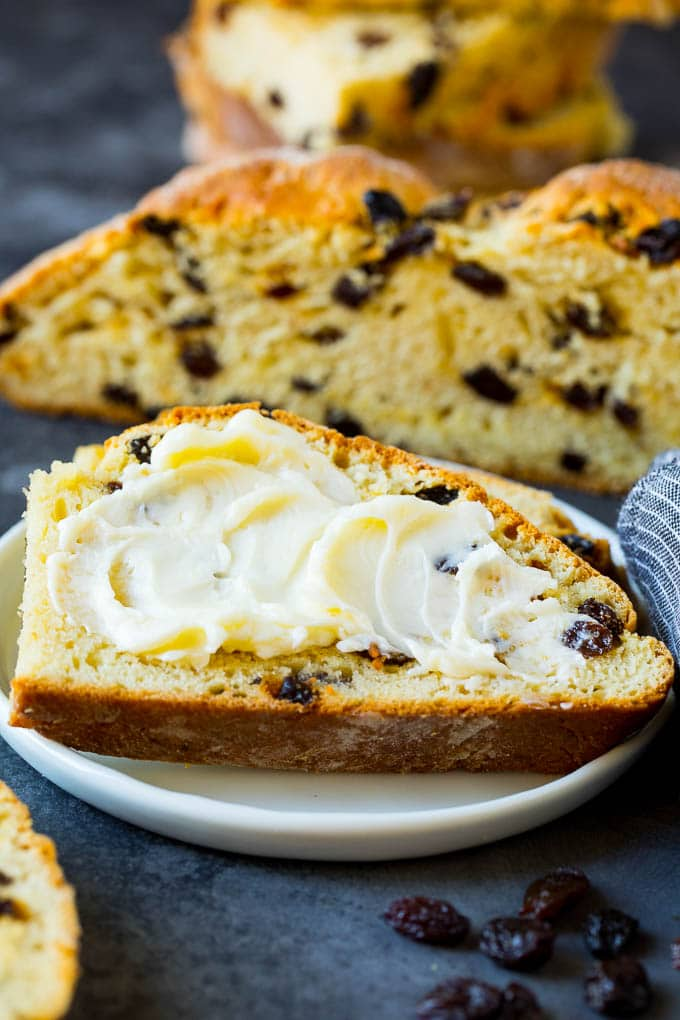 A slice of Irish soda bread with butter spread on it.