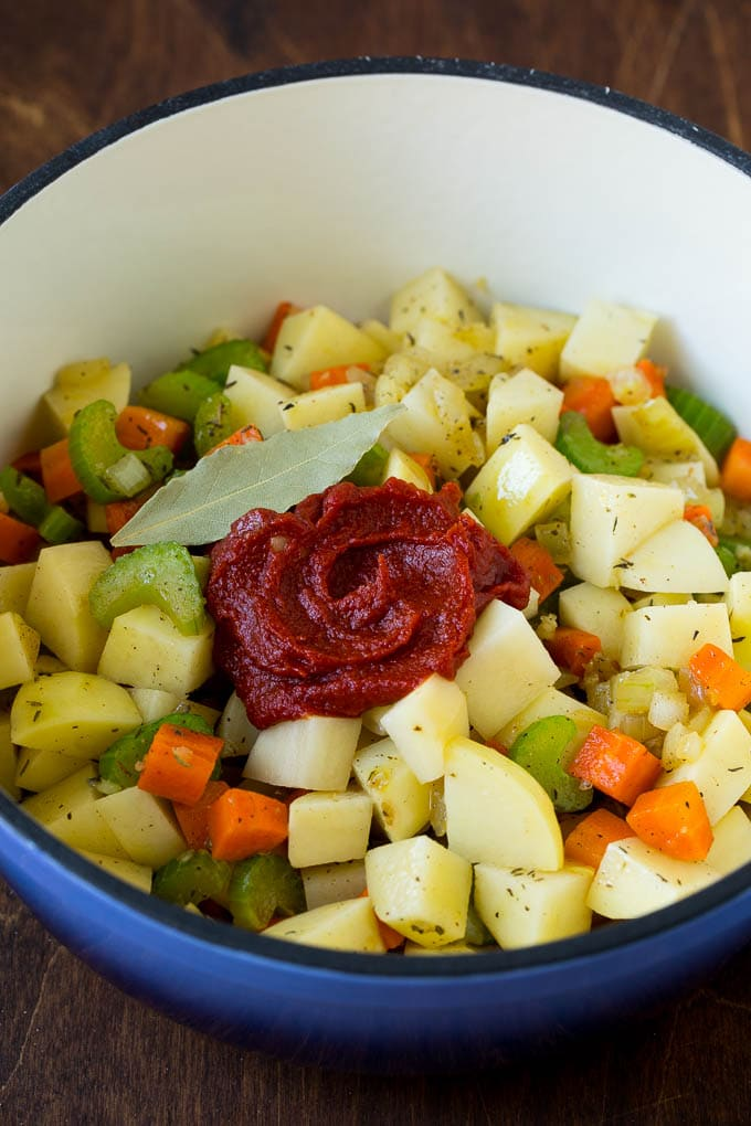 Potatoes, vegetables, herbs and tomato paste in a soup pot.