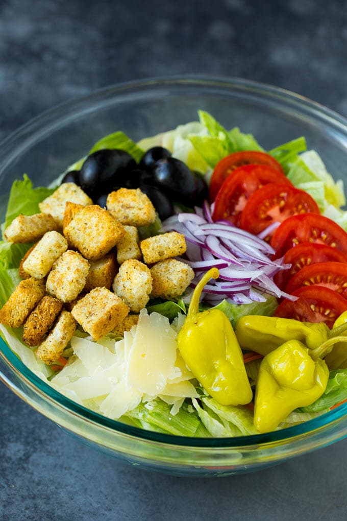 Lettuce, vegetables, olives and croutons in a bowl.