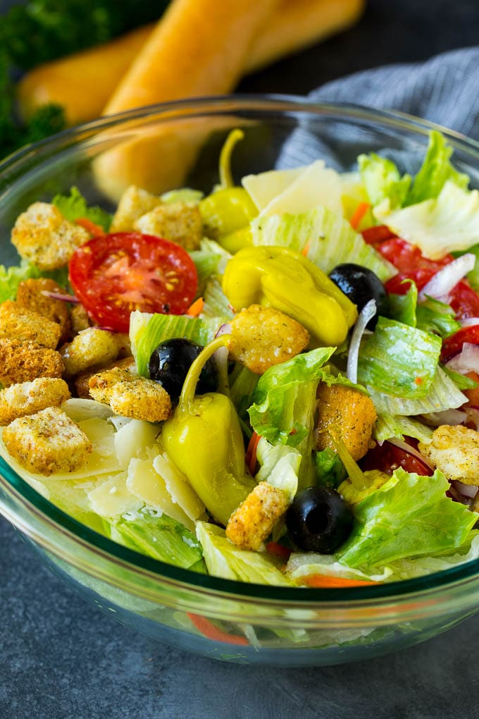 A tossed Olive Garden salad with Italian dressing, vegetables and olives.