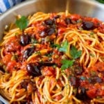 Pasta puttanesca with olives and capers in tomato sauce.