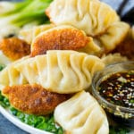 A plate of potstickers served with dipping sauce.