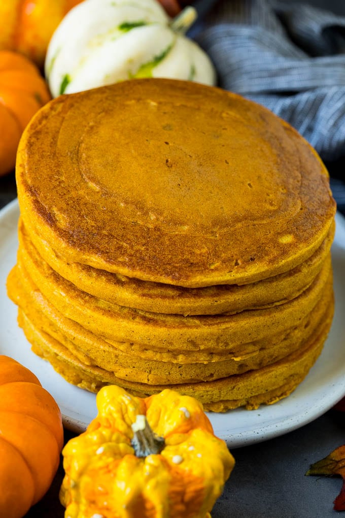 A stack of pancakes surrounded by fall decorations.