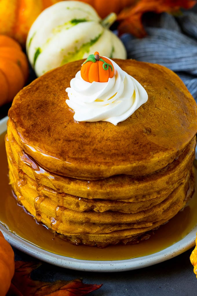 Pumpkin pancakes topped with maple syrup and whipped cream.