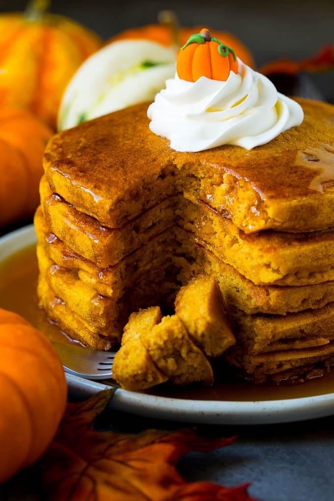 A stack of pumpkin pancakes with a fork holding cut pieces of pancake.
