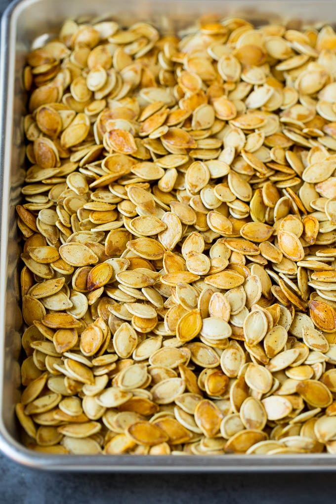 Roasted pumpkin seeds on a sheet pan.