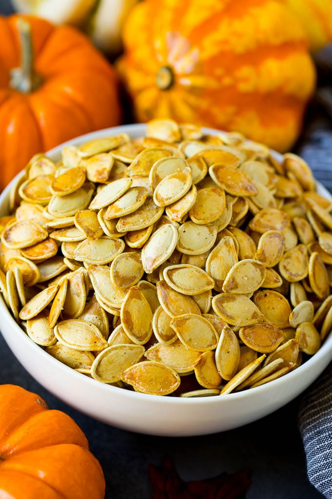 A bowl of roasted pumpkin seeds surrounded by pumpkins and gourds.