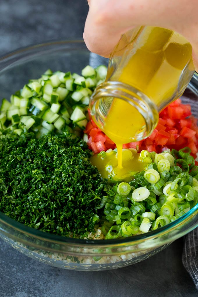 Dressing being poured into a bowl of bulgur wheat salad.