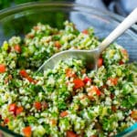 A bowl of tabbouleh with a serving spoon in it.