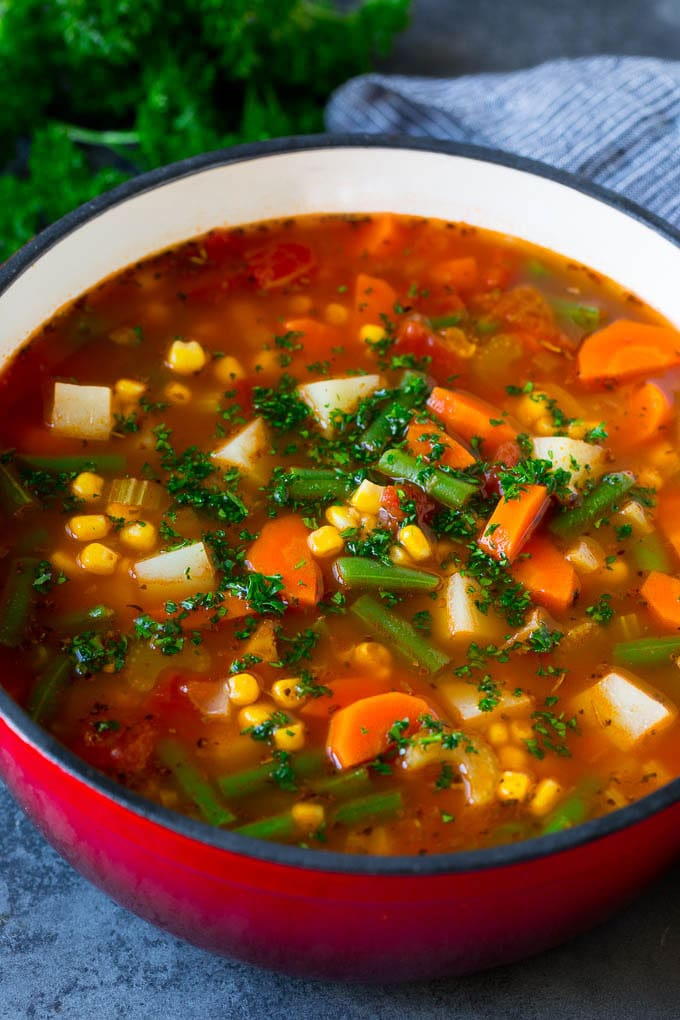 A pot of vegetable soup filled with colorful veggies, potatoes and herbs.
