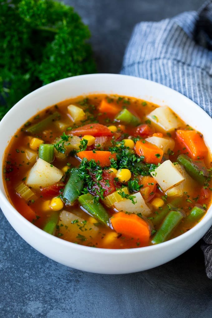 A bowl of vegetable soup with green beans, potatoes, carrots and corn.