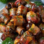 A plate of bacon wrapped dates stuffed with goat cheese.