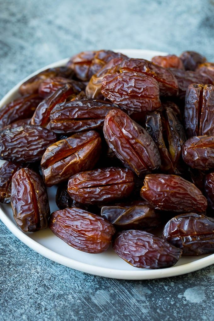 Dates split open on a plate.