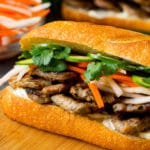 A bahn mi sandwich layered with pork, pickled vegetables and herbs.