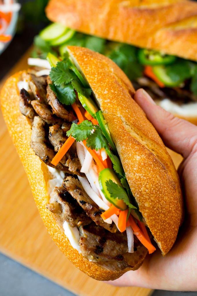 A hand holding a pork banh mi sandwich.