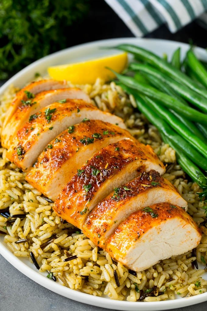 Baked chicken breast served with rice and green beans.
