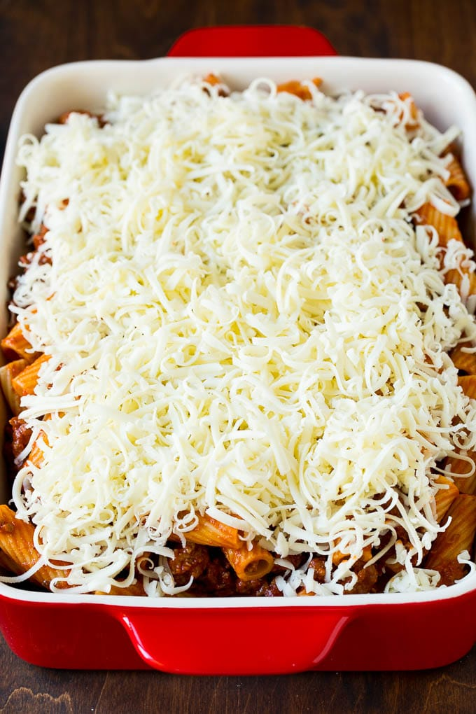 A pan of pasta in sauce topped with shredded cheese.