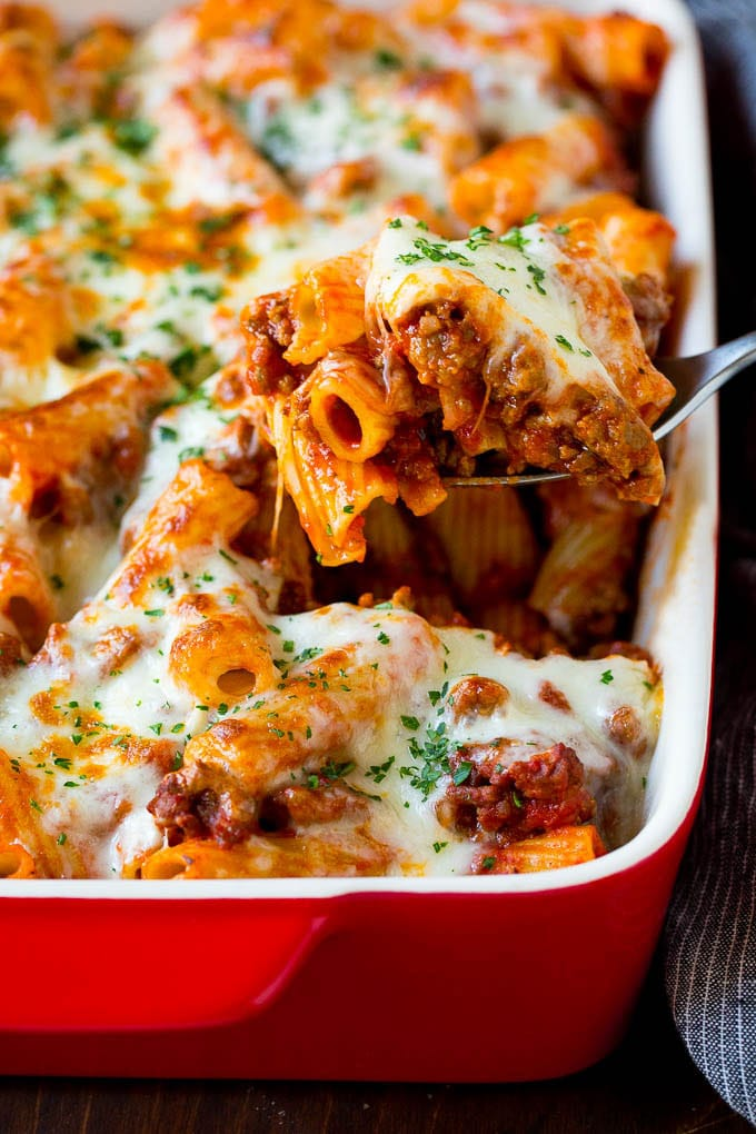 A spoon serving up a portion of baked rigatoni pasta.