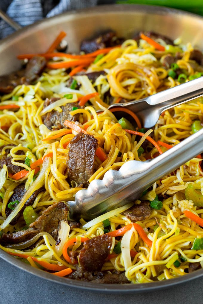 Tongs serving up a portion of beef chow mein.