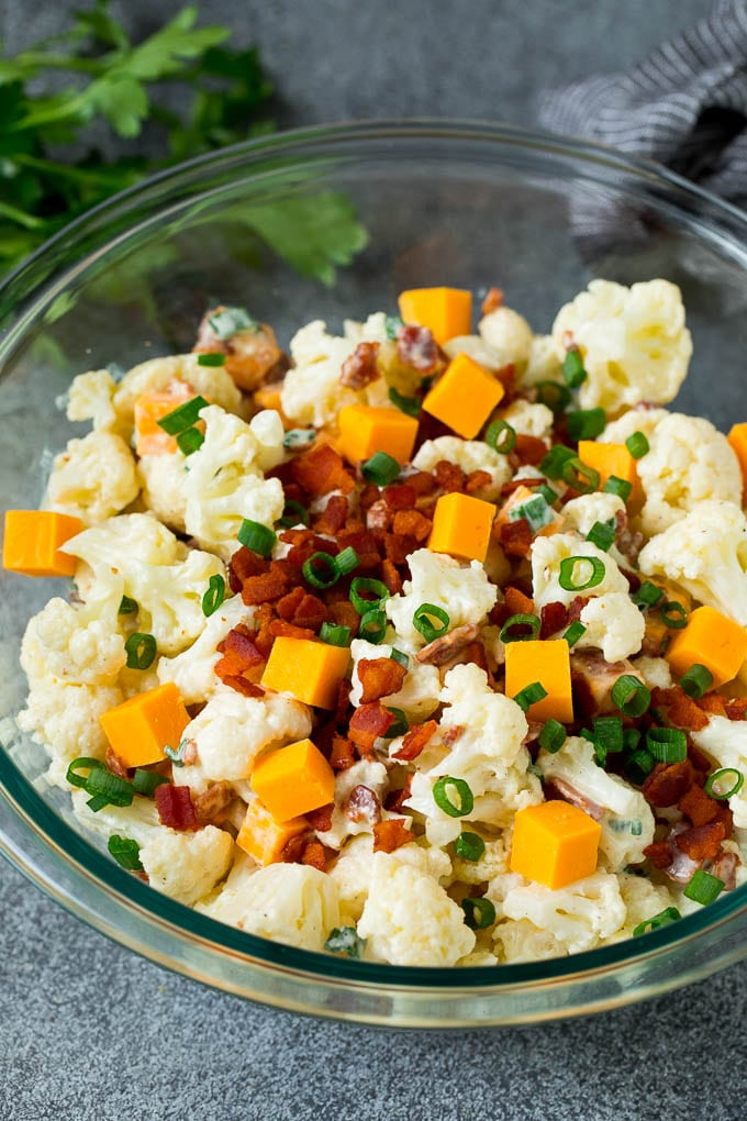 A bowl of cauliflower salad garnished with bacon and green onions.
