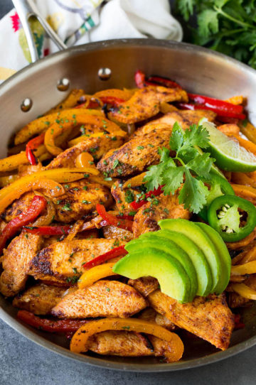 A pan of chicken fajitas with peppers and onions, topped with sliced avocado and cilantro.