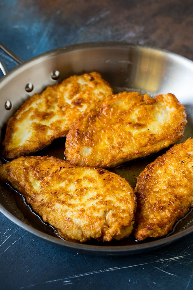 Battered and pan fried chicken cutlets in a pan.