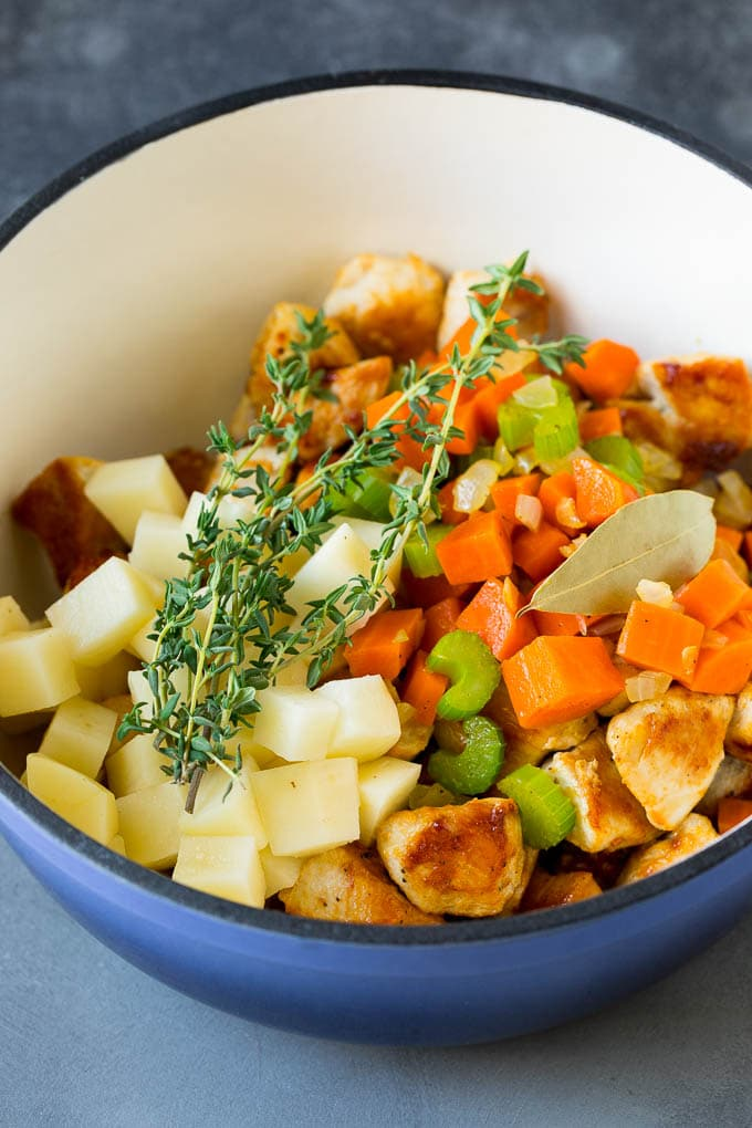 Chicken, vegetables, potatoes and herbs in a pot.