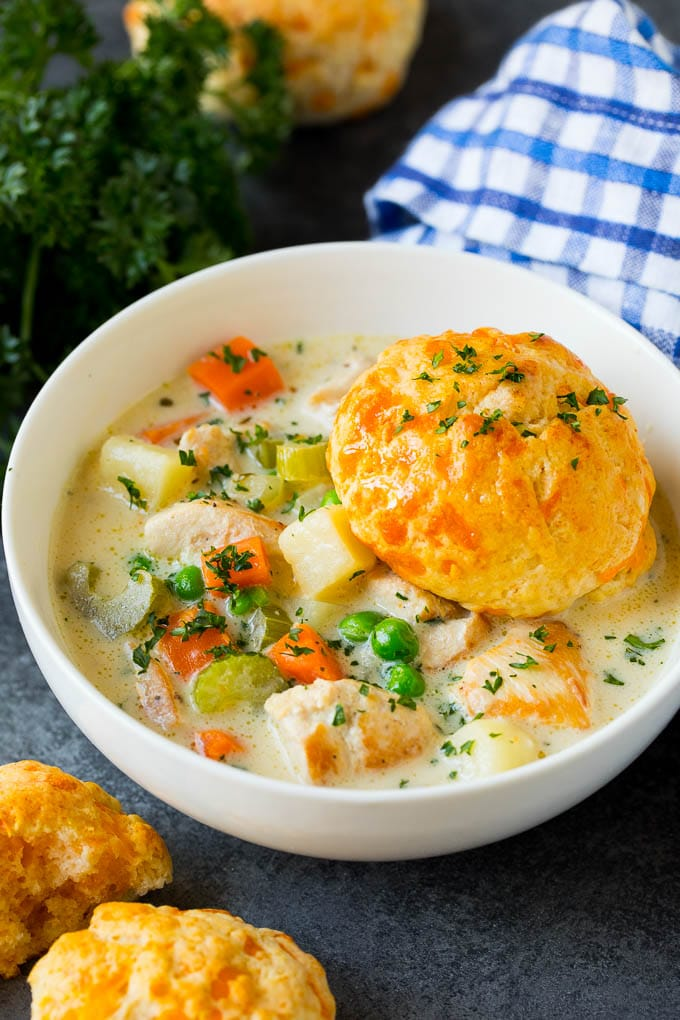 A bowl of chicken pot pie soup with a biscuit on top.