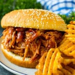 Crockpot BBQ chicken on a bun served with french fries.