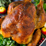 A dry brined turkey garnished with fresh herbs and cranberries.