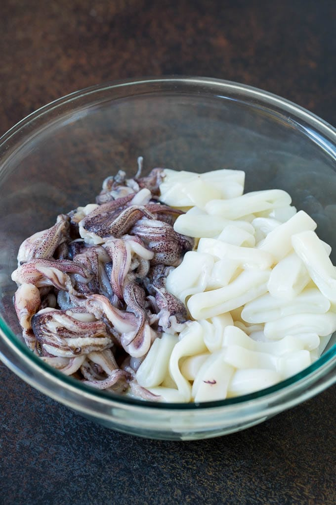 Sliced squid rings and tentacles in a mixing bowl.