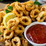 Fried calamari with lemon wedges and a side of cocktail sauce.