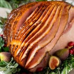 A honey glazed ham on a serving platter, decorated with fruit and herbs.