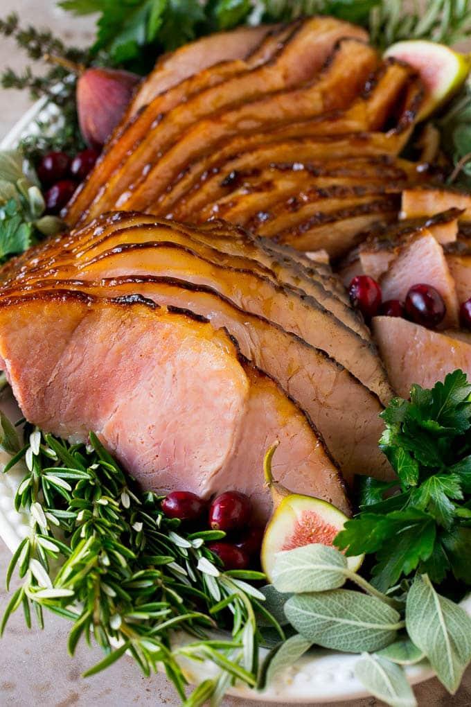 Sliced honey glazed ham on a serving plate.