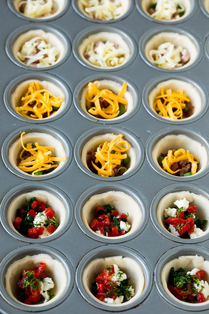 Muffin tins filled with pie crust, vegetables, meat and shredded cheese.