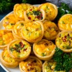 A plate of mini quiche filled with meats, vegetables and cheeses.