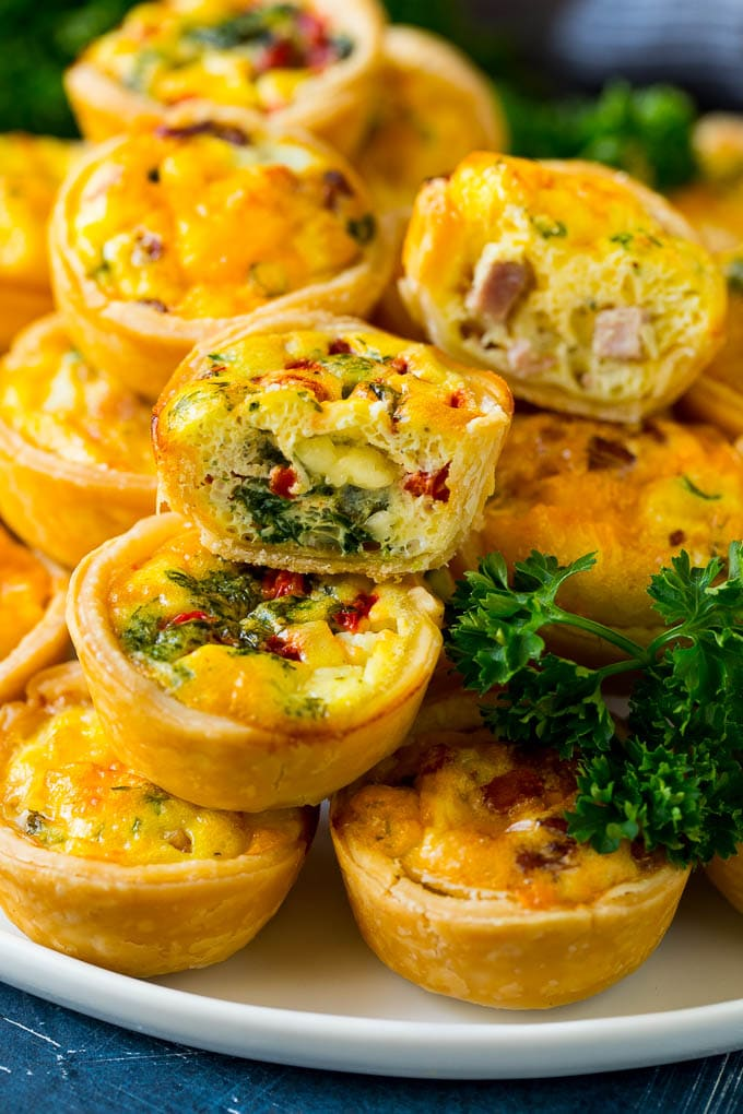A serving platter of mini quiche with some cut in half.