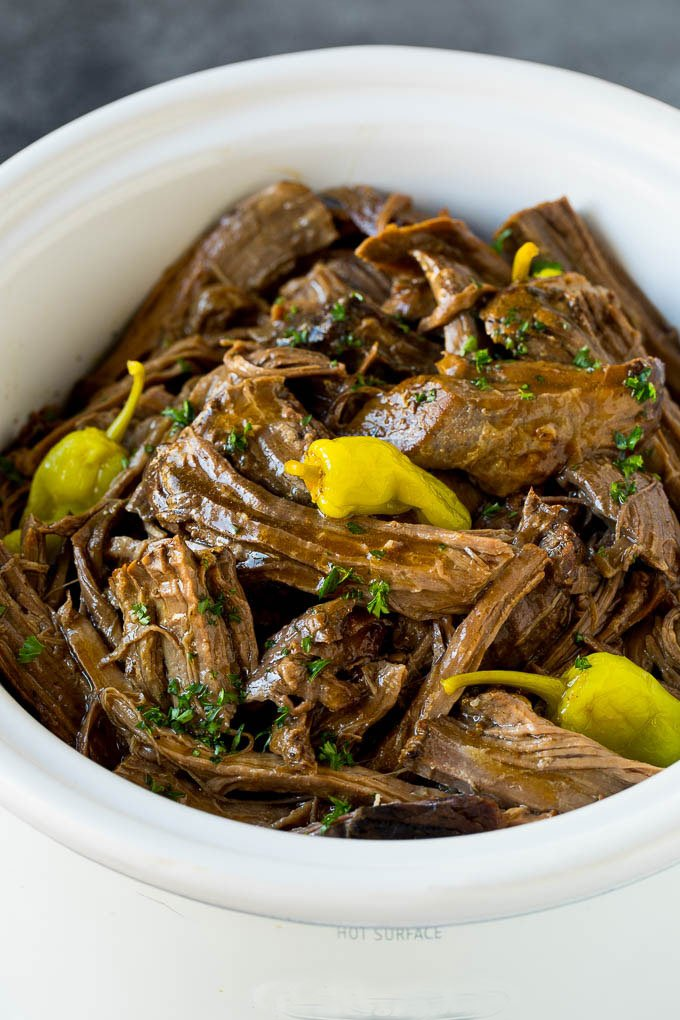 A slow cooker filled with shredded Mississippi pot roast.