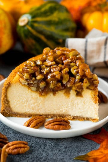 A slice of pecan pie cheesecake on a serving plate.