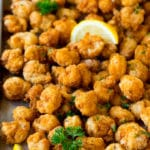 Popcorn shrimp on a sheet pan, garnished with lemon and parsley.