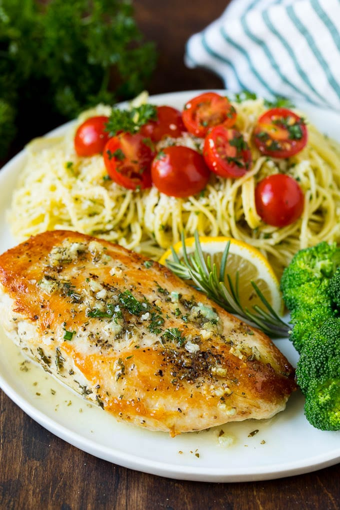 Rosemary chicken on a plate with pasta and broccoli.