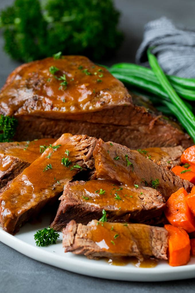 Slow cooker brisket sliced and topped with sauce, served with vegetables.
