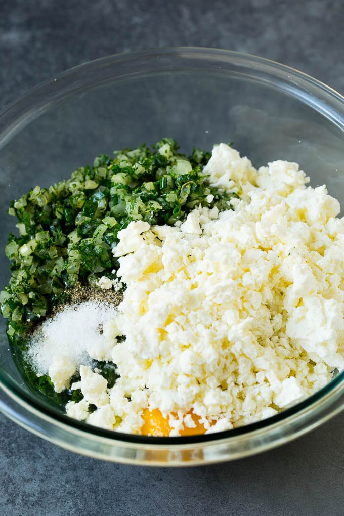 Spinach, onions, herbs and feta cheese in a bowl.