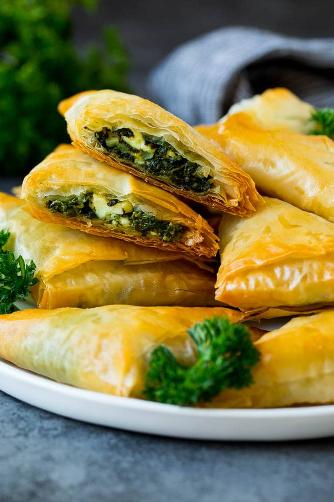A plate of spanakopita with two cut in half.