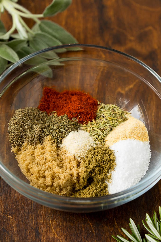 Brown sugar, salt, herbs and spices in a mixing bowl.