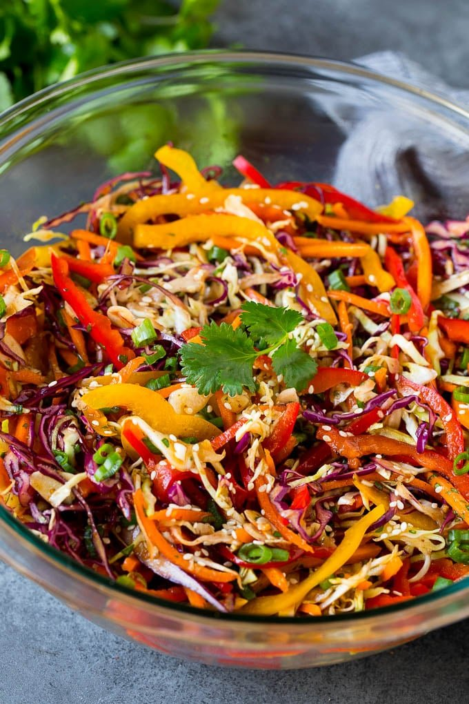 A bowl of Asian slaw garnished with sesame seeds and herbs.