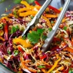 Tongs serving up a portion of Asian slaw.