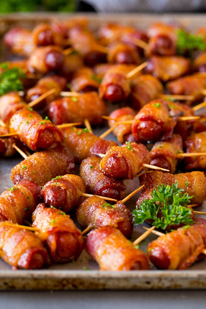 Bacon wrapped smokies on a sheet pan, garnished with fresh parsley.